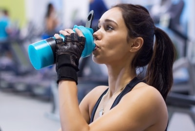 image of woman drinking pre workout drink