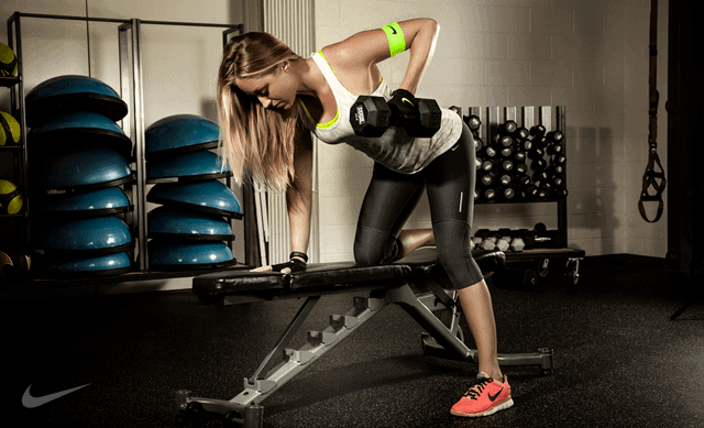 girl doing dumbbell rows on weight bench