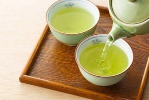 two cups of green tea being filled