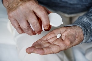 a man popping a pill onto his palm