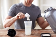 man mixing protein powder in shaker bottle