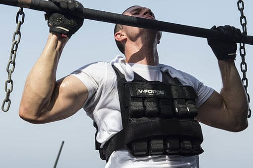 man doing pull-ups with weight training vest