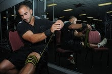 fit guy with wrist support wrapping a knee brace as well
