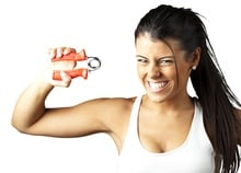 portrait of a pretty sporty woman over white background with grip strengtheners