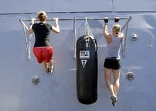 two women doing pull ups together outside