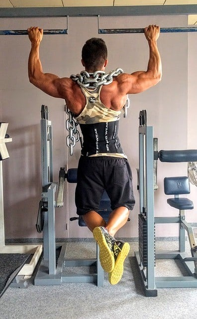 man doing pull ups wearing dip belt and with heavy chain around neck