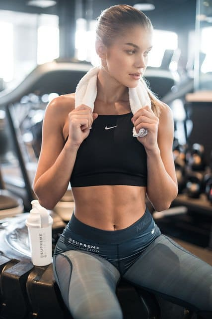 woman sitting down in gym with towel around neck