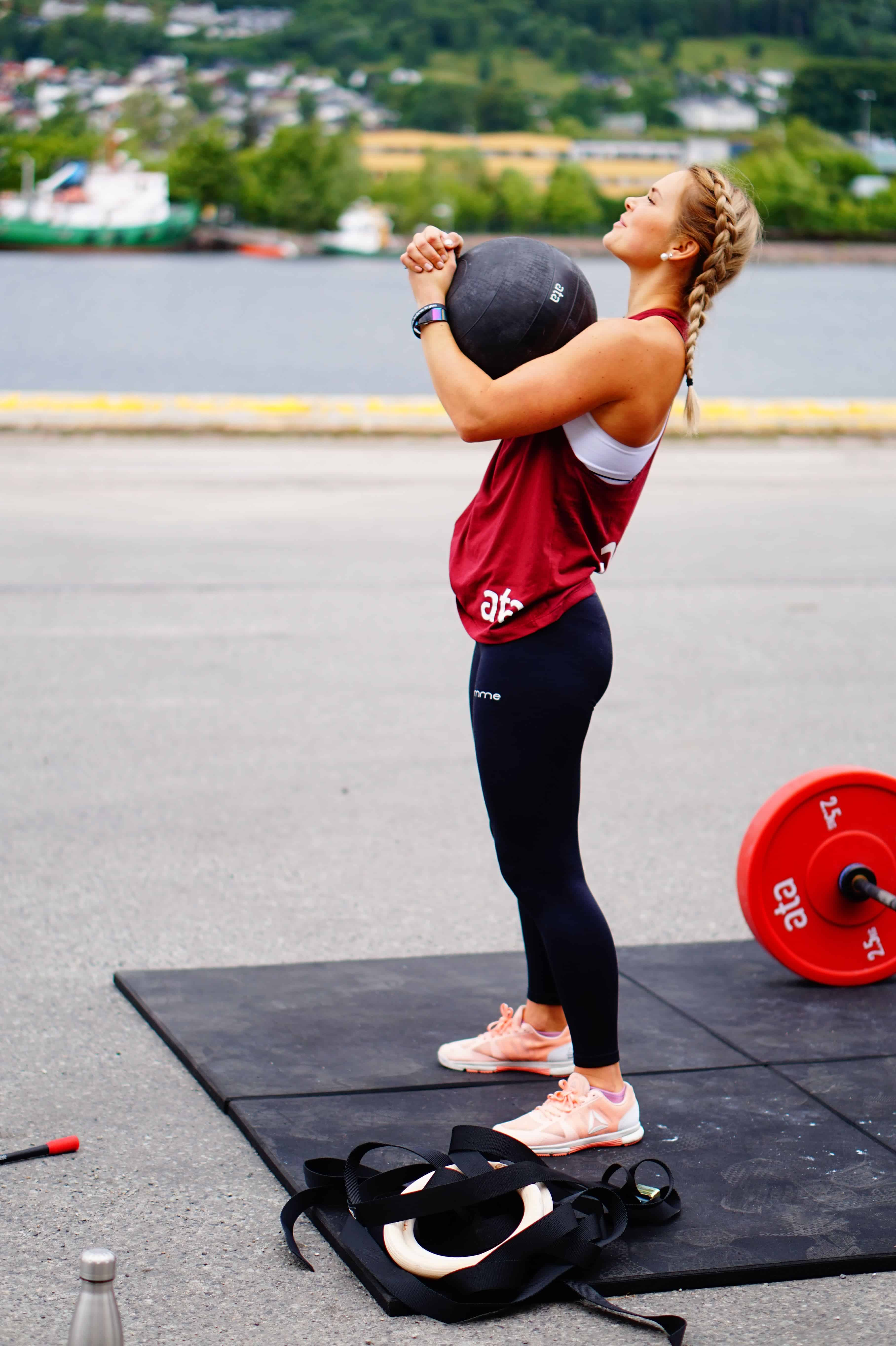 woman holding medicine ball outside on gym mat