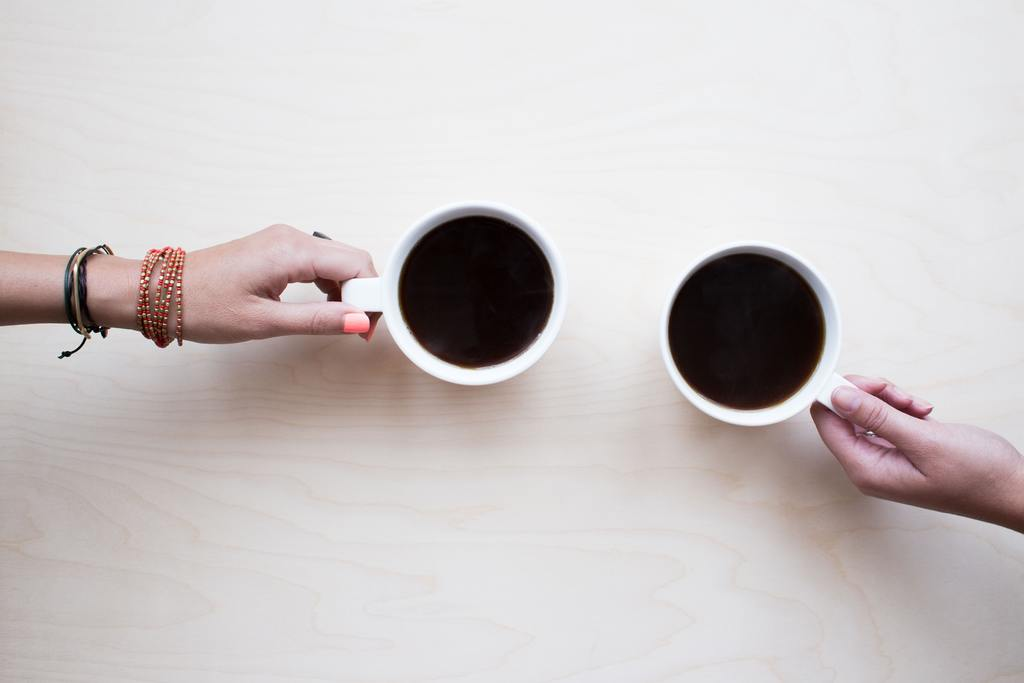white cups of coffee held by a couple