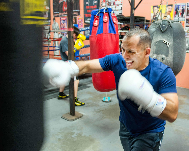 man on intense training wearing heavy bag boxing gloves