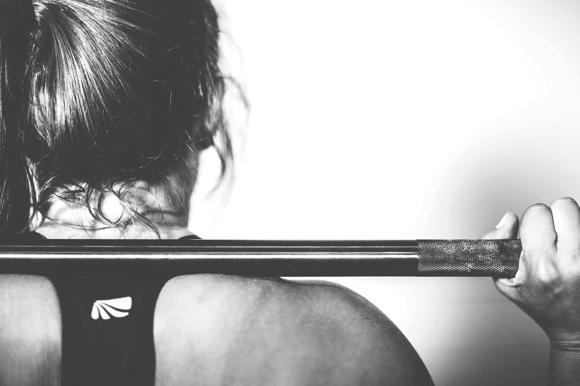 back view of woman lifting barbell